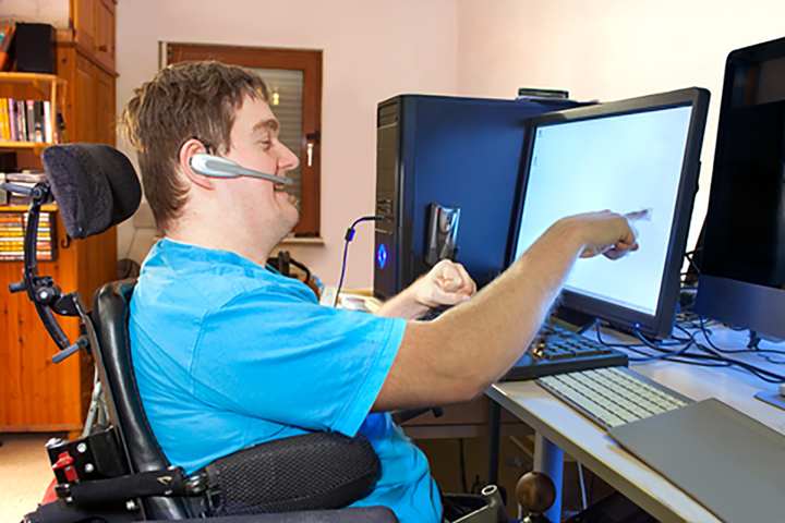 Man with cerebal palsy using a computer.